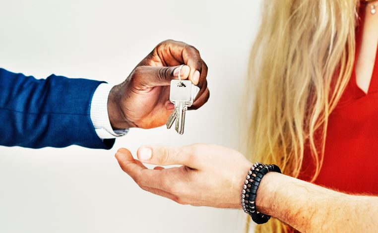 Realtor handing keys to new homeowners