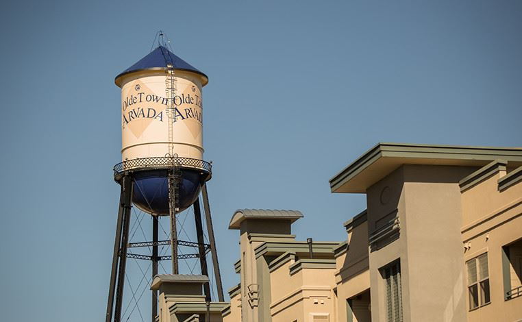 City water tower behind building faces