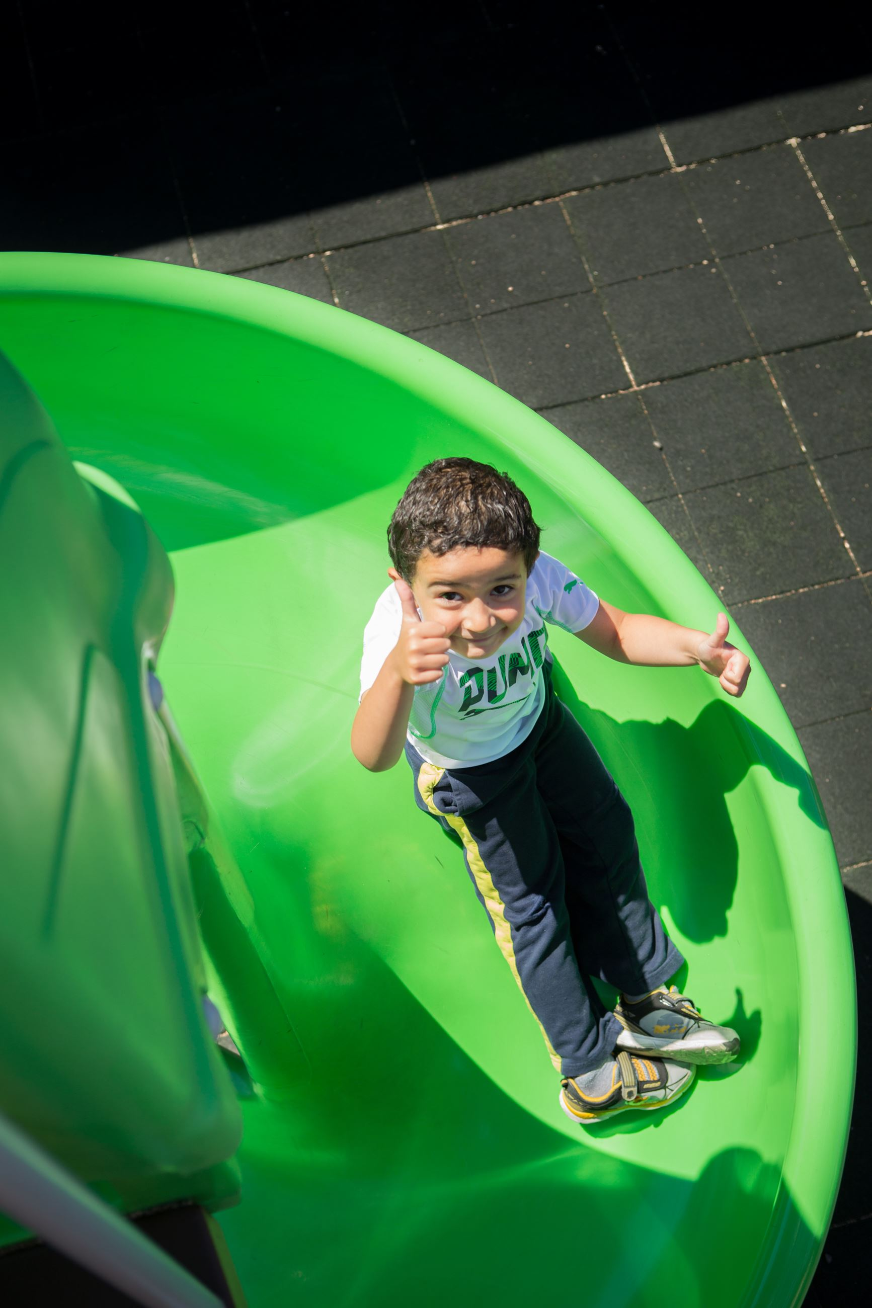 Boy on the slide, giving a thumbs up