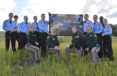Image of nine youth explorers in uniform with four sheriffs in field